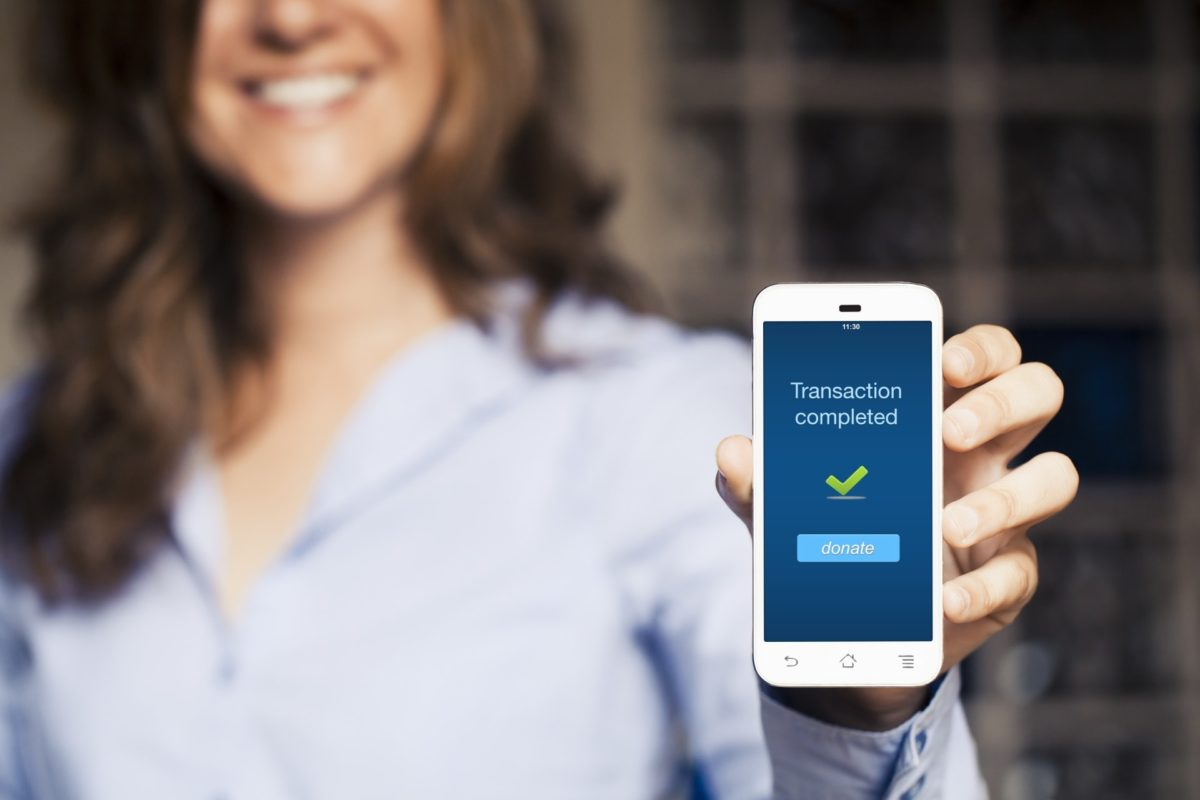 Woman holding smartphone with donation transaction message