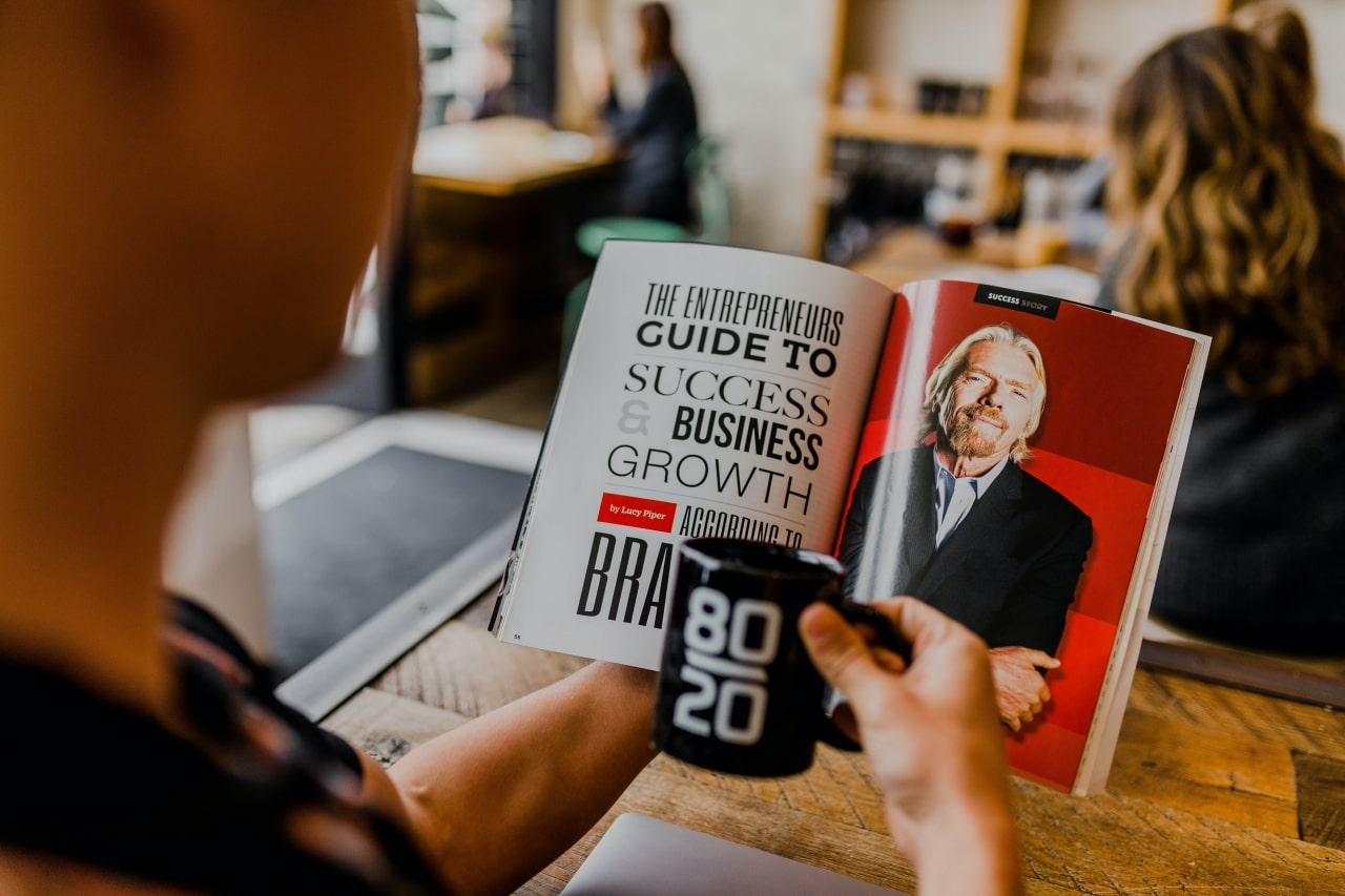 Man reading business strategy article in magazine and holding coffeecup imprinted with 80 20